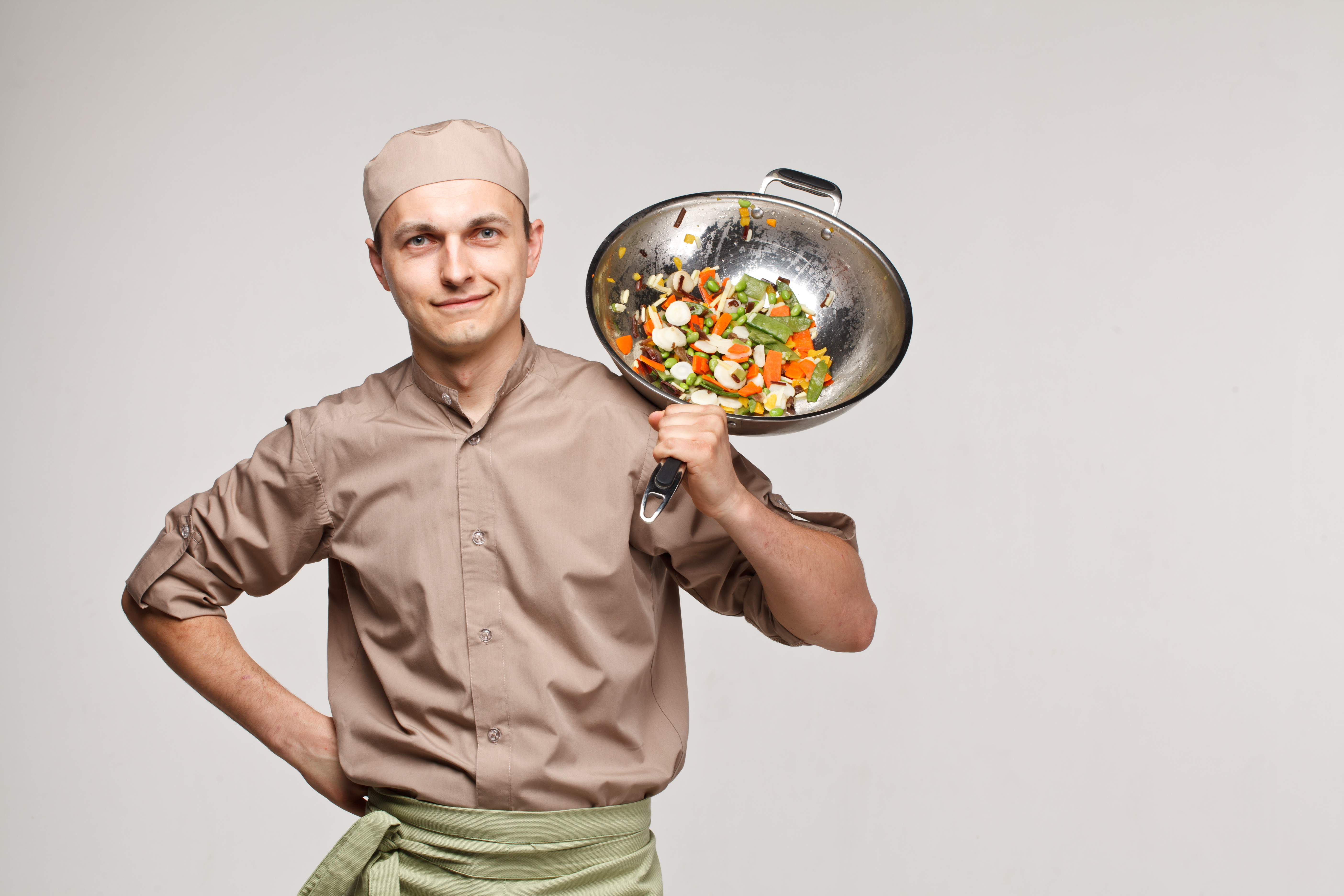 cooker chef tosses vegetables in pan