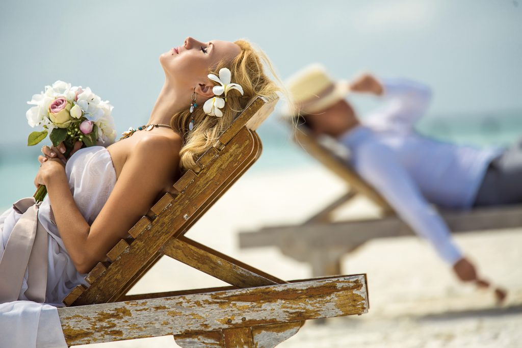 find the perfect honeymoon travel agent the couple lie on the sun loungers on the beach